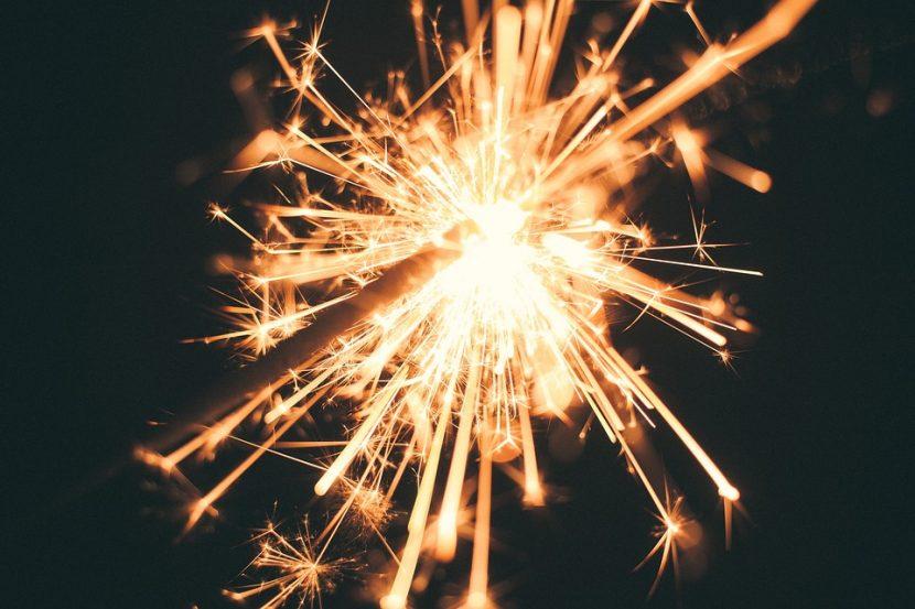 A close up shot of a lit sparkler against a black background.
