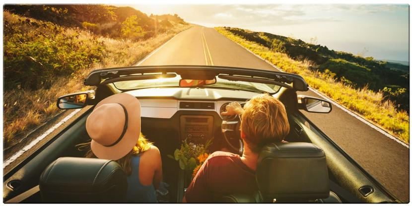 young couple driving down the road on a sunny day