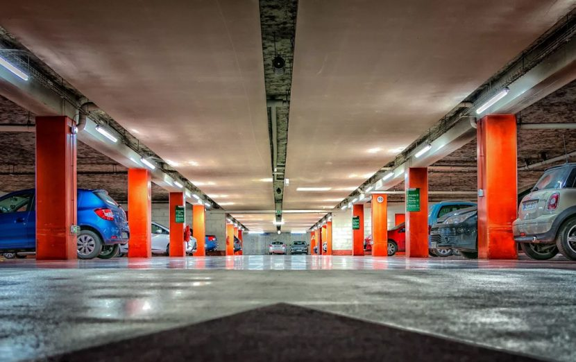 The picture is taken from ground level, looking up across a multistory car park; orange pillars support the ceiling, and a range of different vehicles occupy the parking bays.