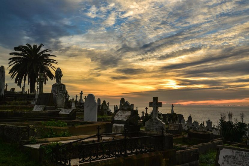 A graveyard with many various headstones stretches out in the foreground, beneath a hazy sunlit sky beside the sea.