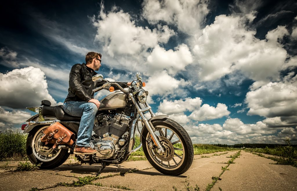 A high contrast photo of a man sat abreast a classic motorbike on an overgrown road beneath a cloudy blue sky.