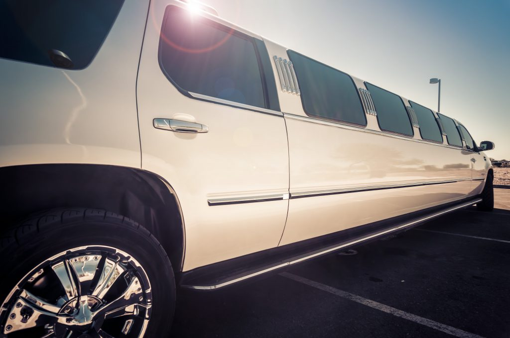 A white stretch limousine parked across a car park under a clear blue sky.