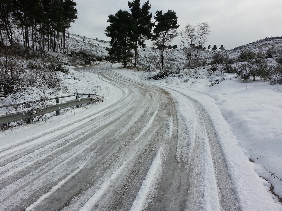 A winding road in the middle of snow covered terrain, with a visibly dangerous road surface that is heavily iced and snow covered.