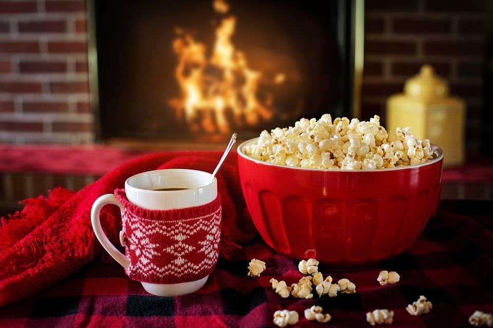 A bowl of popcorn, and a mug of coffee wearing a festive knitted cosy, sit in the foreground upon a tartan blanket, whilst a fireplace is out of focus blazing in the background,