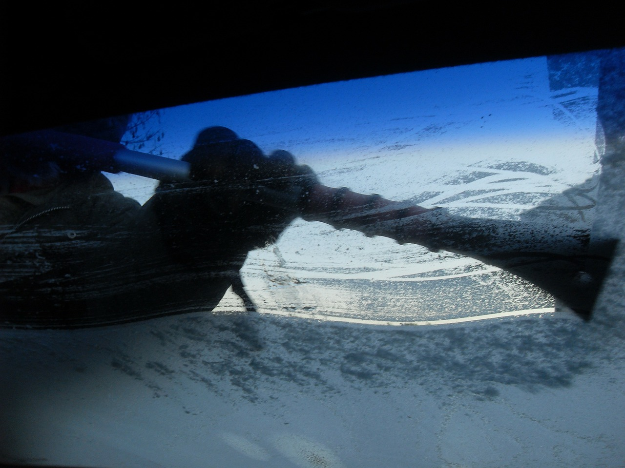 icy car windshield being scraped clear